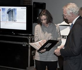 Charles Armstrong, Armstrong's chairman, presenting the photos to Caroline Andrieux, the curator and owner of the gallery.