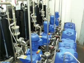 Figure 2a. The centralized coating preparation: (L-R) supply tanks (black); four of the five Bran+Luebbe metering/mixing pumps; coating agent containers (blue).
