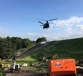 An RAF Chinook flies over one of SLD's hire units on site.