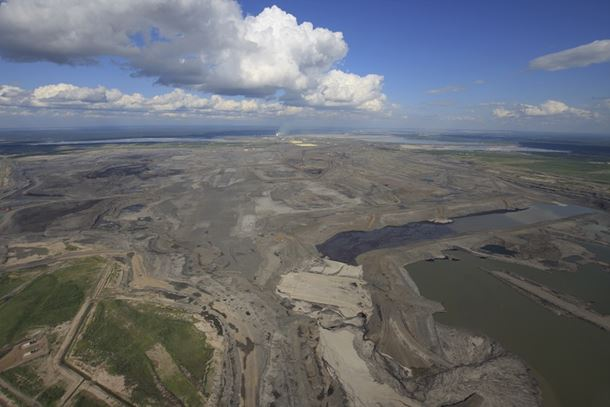 A wide view of an open pit bitumen mining operation in northern Alberta. Large stockpiles of the by-product sulfur (yellow) can be seen in the background. (Image: Donny Ash/Shutterstock)